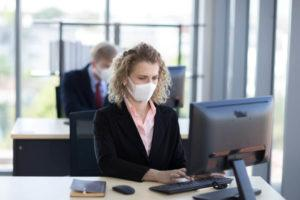 Woman working during the pandemic from the COVID 19 wearing a mask